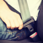 person clicking seatbelt in car